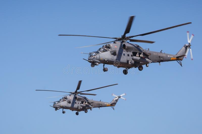 Los pares de los helicópteros de ataque rusos modernos MI-35M realizan vuelos de la demostración en el cielo sobre un terreno de  imágenes de archivo libres de regalías