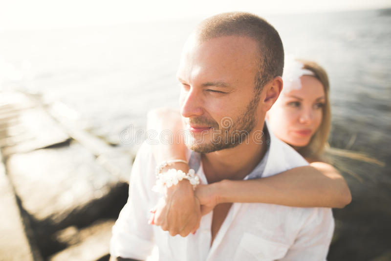 Los pares de la boda que se besan y que abrazan en rocas acercan al mar azul imagen de archivo