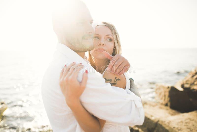 Los pares de la boda que se besan y que abrazan en rocas acercan al mar azul fotografía de archivo libre de regalías