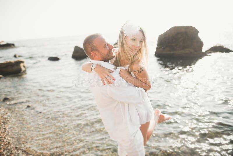 Los pares de la boda que se besan y que abrazan en rocas acercan al mar azul imagen de archivo libre de regalías