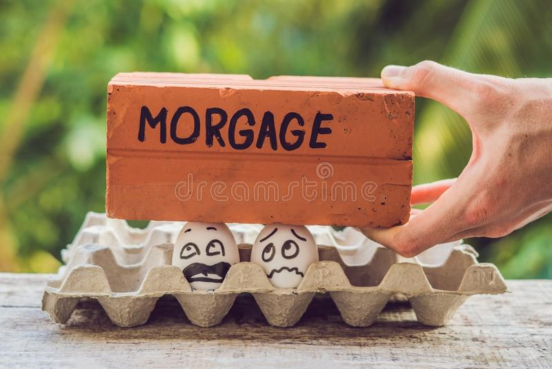 Los pares de la familia bajo la forma de dos huevos tienen un problema con una hipoteca imagen de archivo libre de regalías