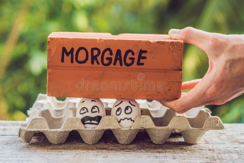 Los pares de la familia bajo la forma de dos huevos tienen un problema con una hipoteca imágenes de archivo libres de regalías