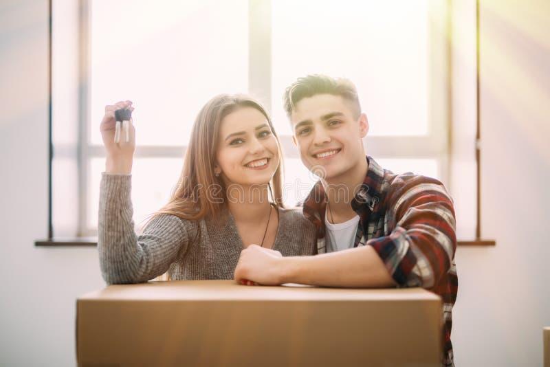 Los pares de la sonrisa de los jóvenes se sientan en el piso alrededor de las cajas que llevan a cabo llave disponible fotos de archivo libres de regalías