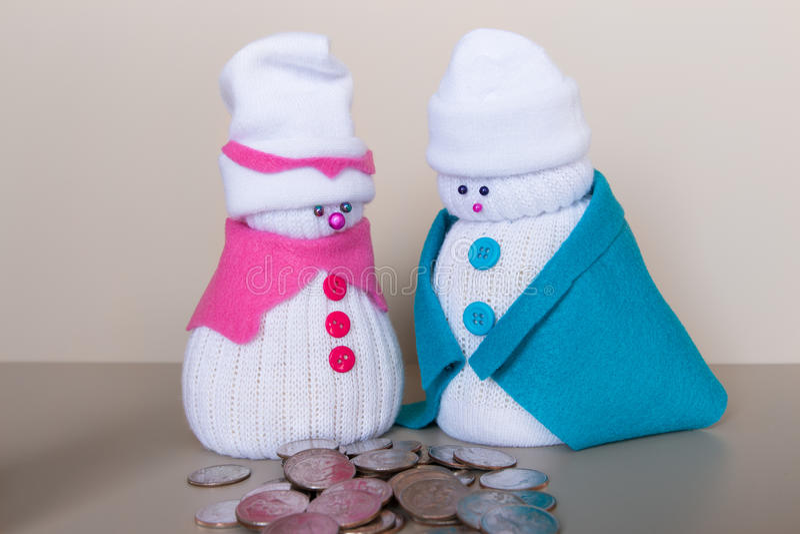 Los pares de los muñecos de nieve del juguete miran la pila de monedas fotografía de archivo