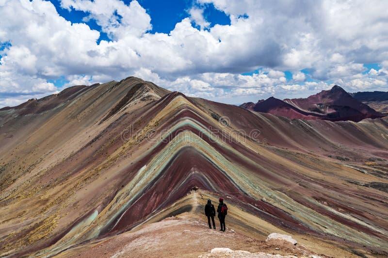 Los pares de los turistas se colocan y miran lejos las montañas del arco iris, Cusco, Perú imágenes de archivo libres de regalías