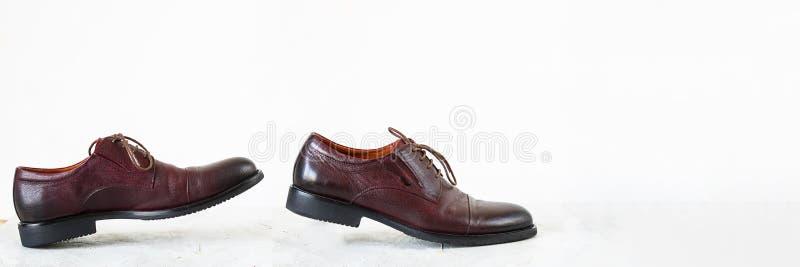 Los pares de mofa cl?sica marr?n encima de los zapatos del hombre caminan en piso texturizado gris del cemento y en el fondo blan fotografía de archivo libre de regalías