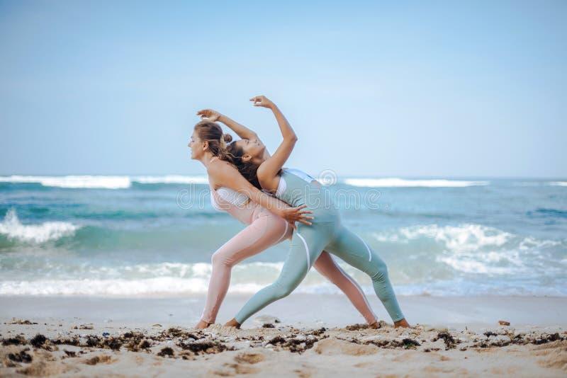Los pares de muchachas practican yoga contra la perspectiva del océano imágenes de archivo libres de regalías