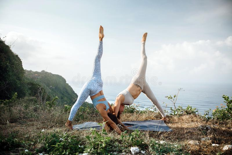 Los pares de muchachas practican yoga contra la perspectiva del océano fotografía de archivo