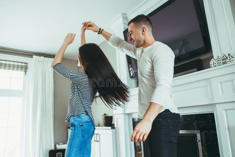 los pares de risa sonrientes de los jóvenes románticos sirven a la mujer en el amor que abraza, el besarse, bailando juntos imagen de archivo libre de regalías
