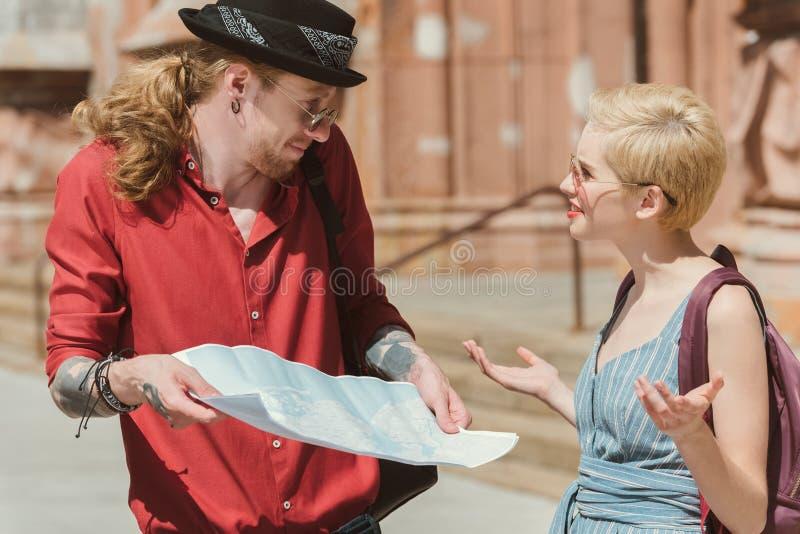 los pares de viajeros consiguieron perdidos y que sostenían el mapa fotografía de archivo