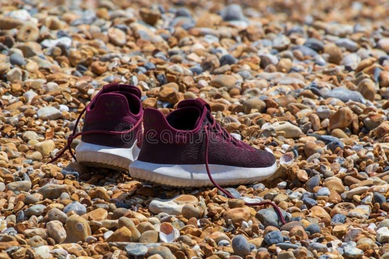Los pares de zapatillas deportivas están esperando su amo en la costa mientras que él participa en una cierta clase de aventuras foto de archivo