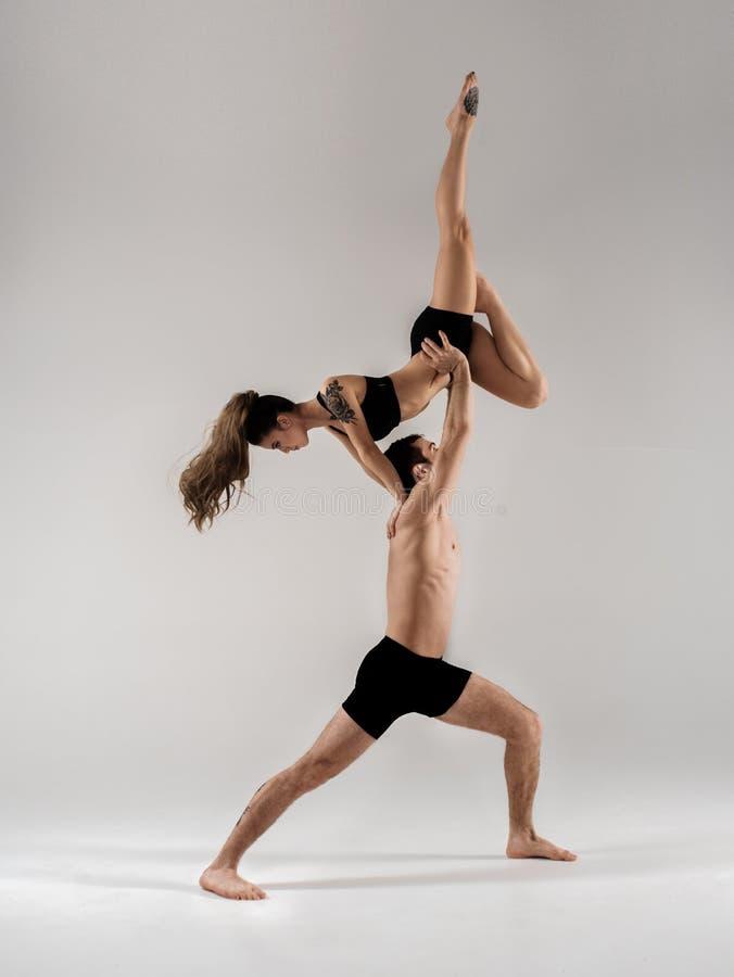 Los pares del bailarín de ballet moderno en arte interpretativa de la forma negra saltan con el fondo vacío del espacio de la cop fotos de archivo