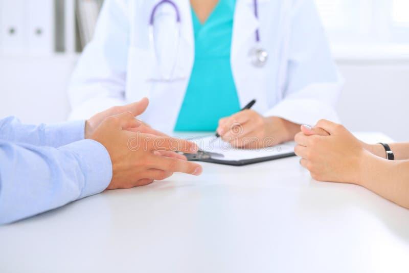 Los pares del doctor y del paciente están discutiendo algo, apenas manos en la tabla imagenes de archivo