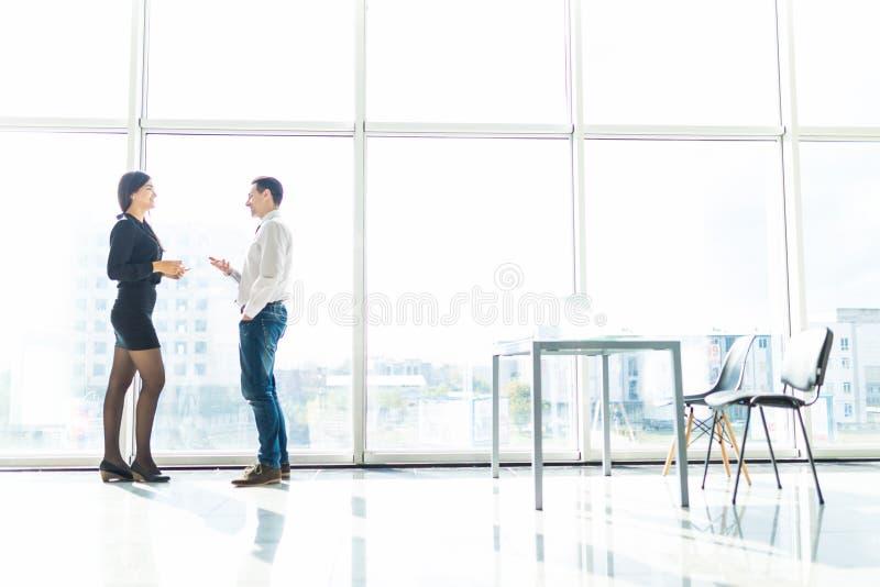 Los pares del hombre de negocios, mujer hablan de la herramienta del objeto document en sitio de la oficina contra ventana del ci foto de archivo libre de regalías