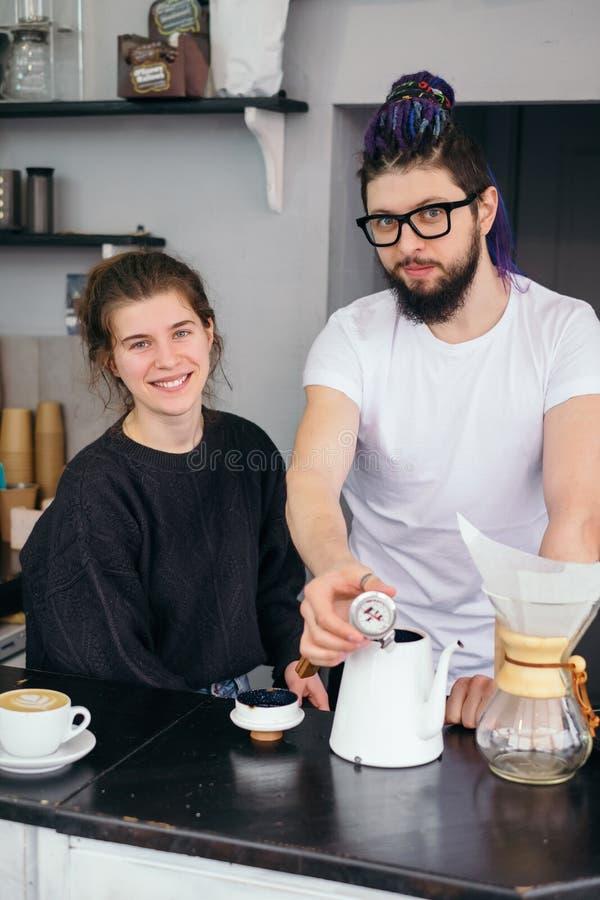 Los pares del inconformista tienen una pequeña empresa y hacen el café fotografía de archivo libre de regalías
