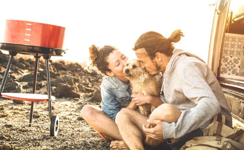 Los pares del inconformista y perro lindo que se relajan por viaje en mini transporte de la furgoneta del oldtimer - vaga el conc foto de archivo libre de regalías