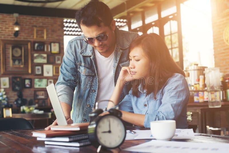 Los pares del negocio trabajan con el ordenador portátil juntos en el café imagen de archivo