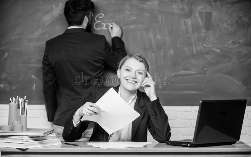 los pares del negocio utilizan el ordenador port?til y documentos Papeleo Vida de la oficina Profesor y estudiante en examen De n imágenes de archivo libres de regalías