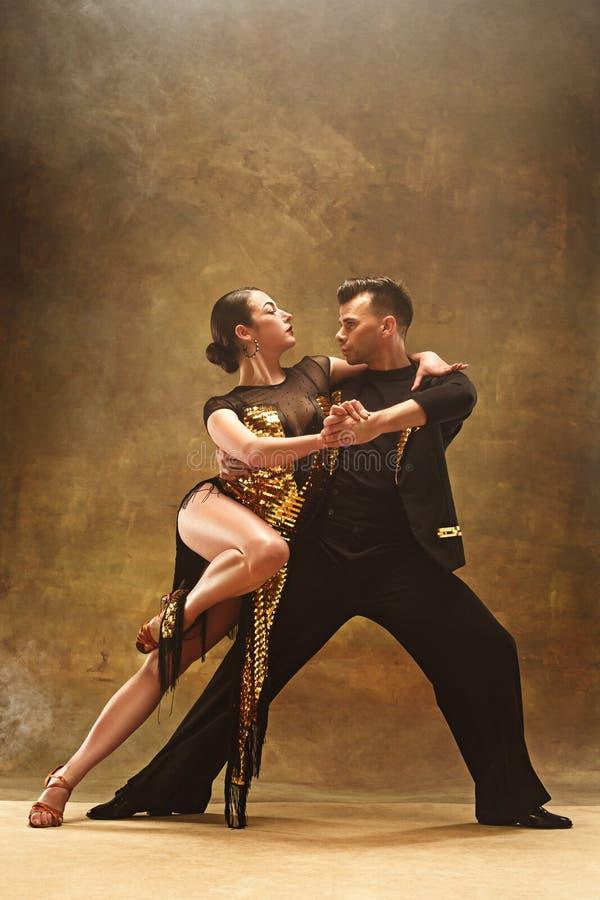 Los pares del salón de baile de la danza en oro visten el baile en fondo del estudio fotografía de archivo