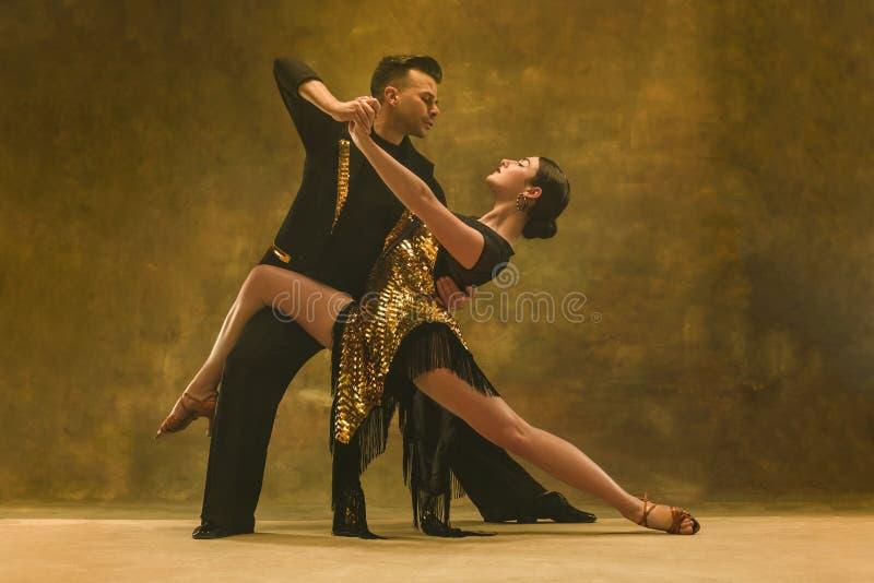 Los pares del salón de baile de la danza en oro visten el baile en fondo del estudio fotos de archivo