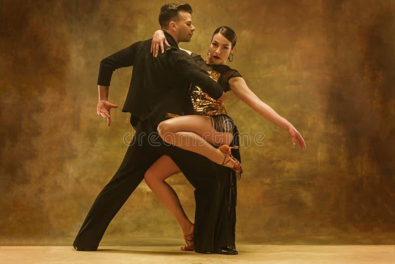 Los pares del salón de baile de la danza en oro visten el baile en fondo del estudio imagen de archivo libre de regalías