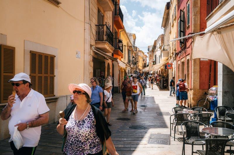 Los pares del turista que caminan a lo largo de una calle de Alcudia y comen el helado, Mallorca imagen de archivo libre de regalías