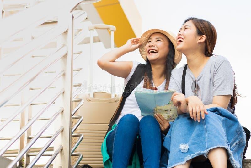 Los pares del viajero con las mochilas se sientan en la escalera usando mapa local genérico juntos el día soleado fotos de archivo