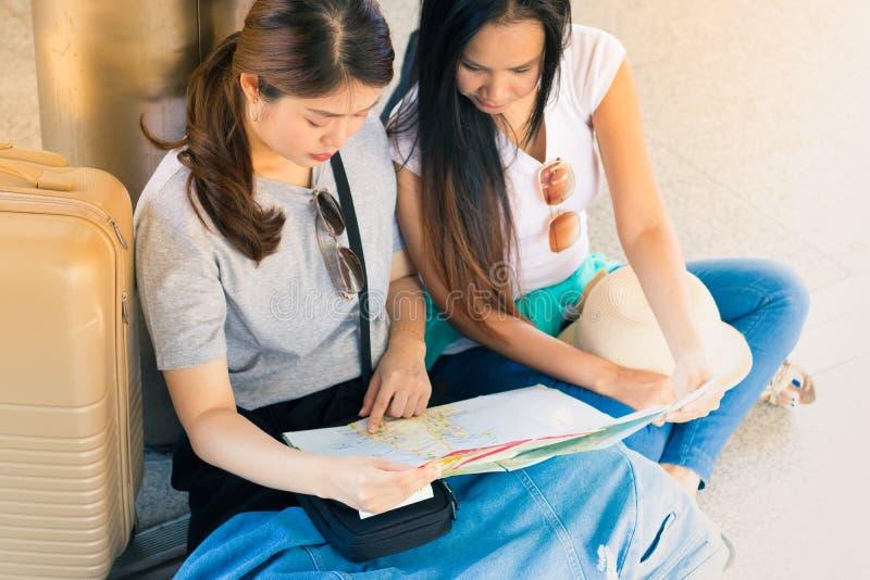 Los pares del viajero con las mochilas se sientan en piso usando mapa local genérico juntos el día soleado imagen de archivo libre de regalías