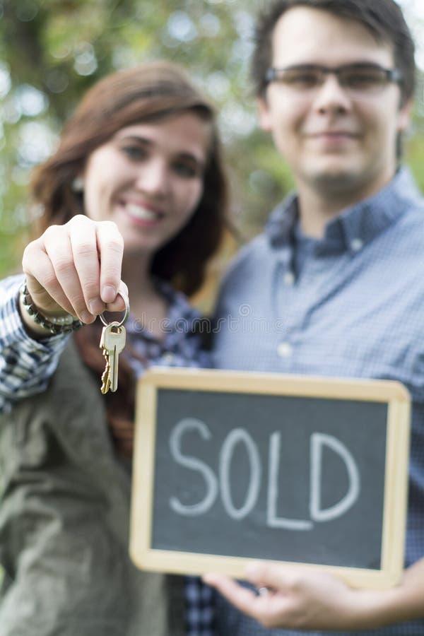 Los pares delante de la nueva tenencia del hogar vendieron la muestra y llaves de la pizarra imagen de archivo