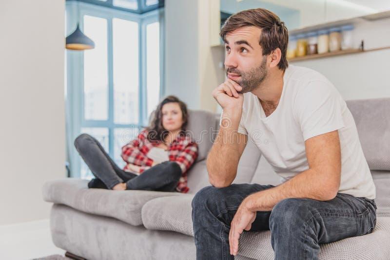 Los pares discuten La esposa gritó a su marido desesperado, sentándose en el sofá en la sala de estar en casa Un hombre no hace imagen de archivo