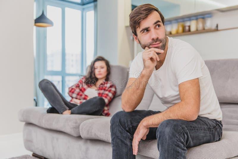 Los pares discuten La esposa gritó a su marido desesperado, sentándose en el sofá en la sala de estar en casa Un hombre no hace foto de archivo