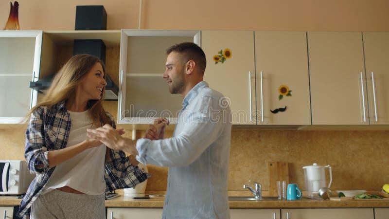 Los pares divertidos jovenes atractivos tienen baile de la diversión mientras que cocinan en la cocina en casa imagen de archivo