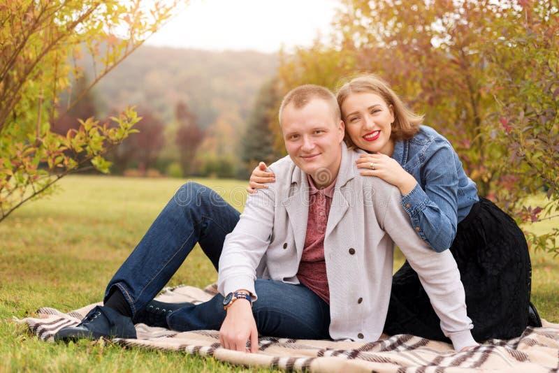 Los pares, el hombre y la mujer felices en otoño parquean sentarse en una tela escocesa Pares sonrientes hermosos que disfrutan d fotos de archivo libres de regalías