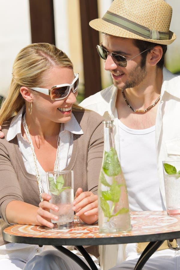 Los pares elegantes de la terraza del restaurante beben día asoleado fotos de archivo