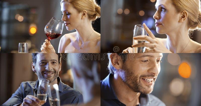 Los pares elegantes románticos sirven la datación de la mujer en el vino de consumición del restaurante gente sonriente de la cen fotografía de archivo