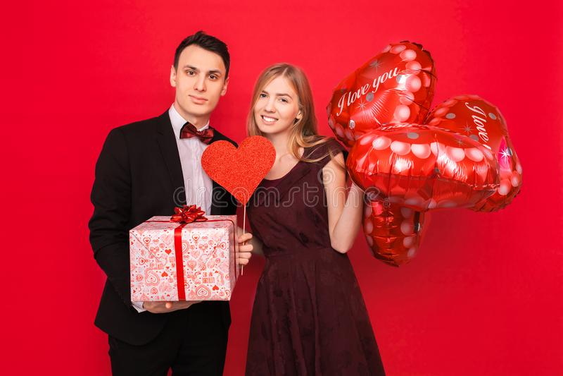 Los pares en amor, hombre y mujer se dan los regalos, sosteniendo las cajas de regalo y los globos, en un concepto rojo del día d fotografía de archivo