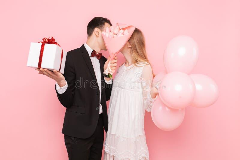 Los pares en amor, se dan los regalos, besándose, ocultando detrás de un ramo de flores, en un fondo rosado, del día de tarjeta d foto de archivo