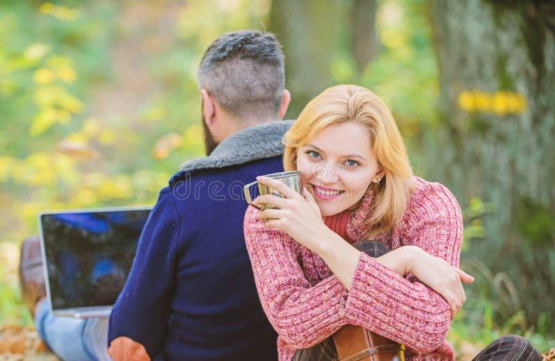Los pares en amor se relajan en bosque del oto?o con el ordenador port?til El acampar y el caminar caf? caliente o vino de la beb foto de archivo