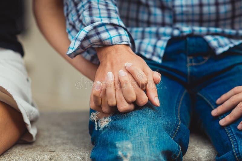 Los pares en amor tocaron las manos la primera fecha Hombre en driles de algodón fotografía de archivo libre de regalías