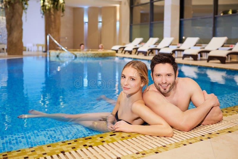 Los pares en bañadores en el balneario de reclinación de la piscina se centran fotografía de archivo