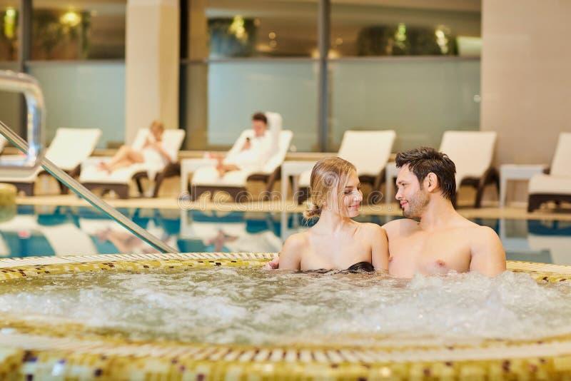 Los pares en bañadores en el balneario de reclinación de la piscina se centran foto de archivo libre de regalías