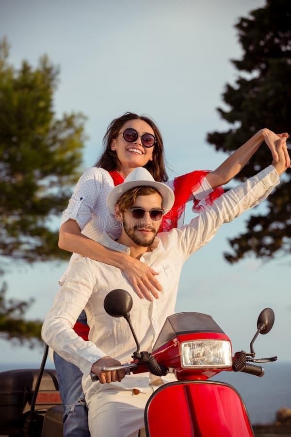 Los pares en el amor que monta una moto, un individuo hermoso y a una mujer atractiva joven viajan imagenes de archivo