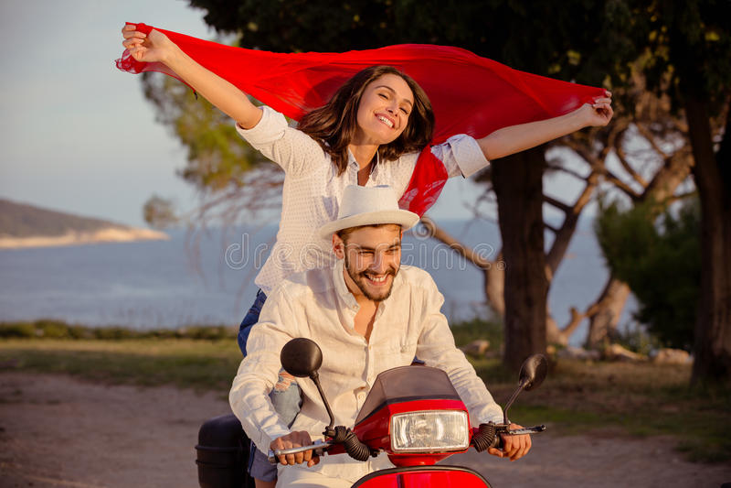 Los pares en el amor que monta una moto, un individuo hermoso y a una mujer atractiva joven viajan fotografía de archivo libre de regalías