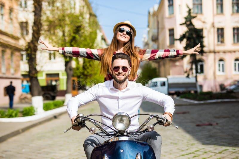 Los pares en el amor que monta una moto, un individuo hermoso y a una mujer atractiva joven viajan Jinetes jovenes que se gozan e foto de archivo libre de regalías