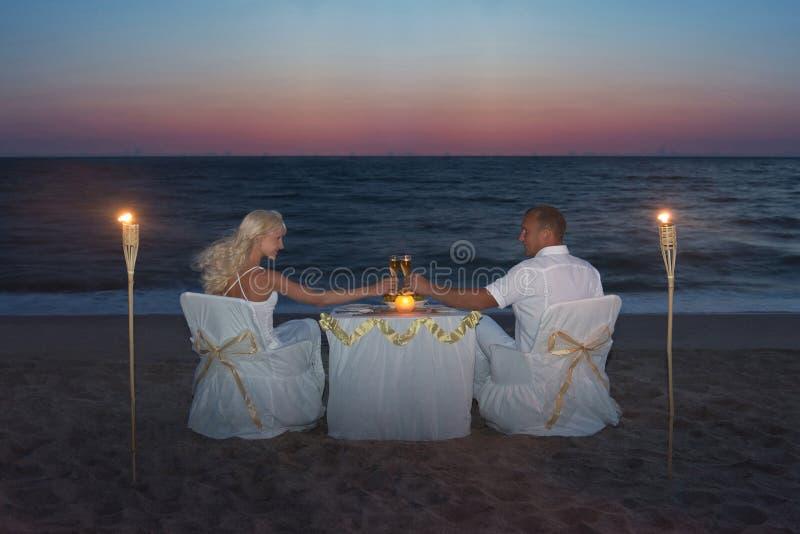 Los pares en el mar varan durante cena romántica de lujo, con las velas fotos de archivo libres de regalías