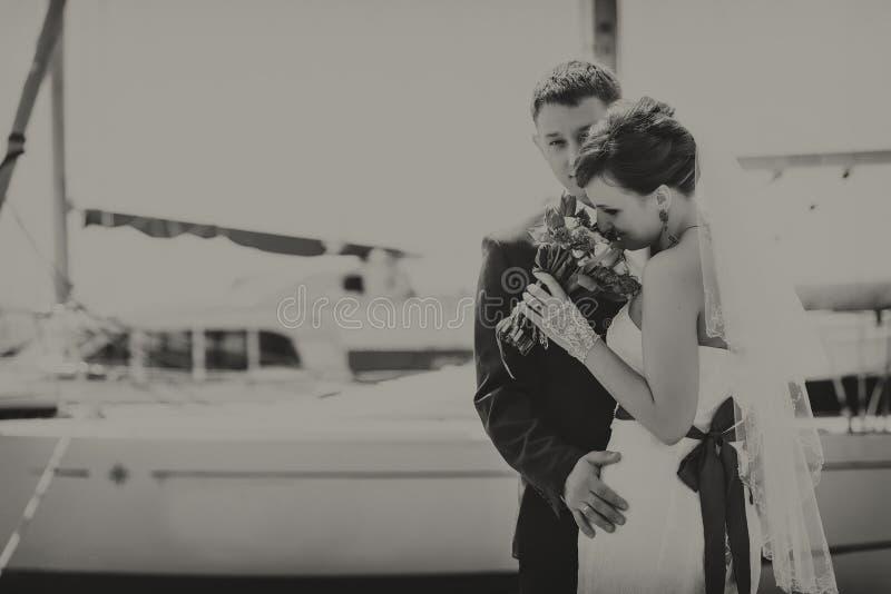 Los pares en el puerto, abrazándose, mirando el ramo Fotografía blanco y negro fotografía de archivo