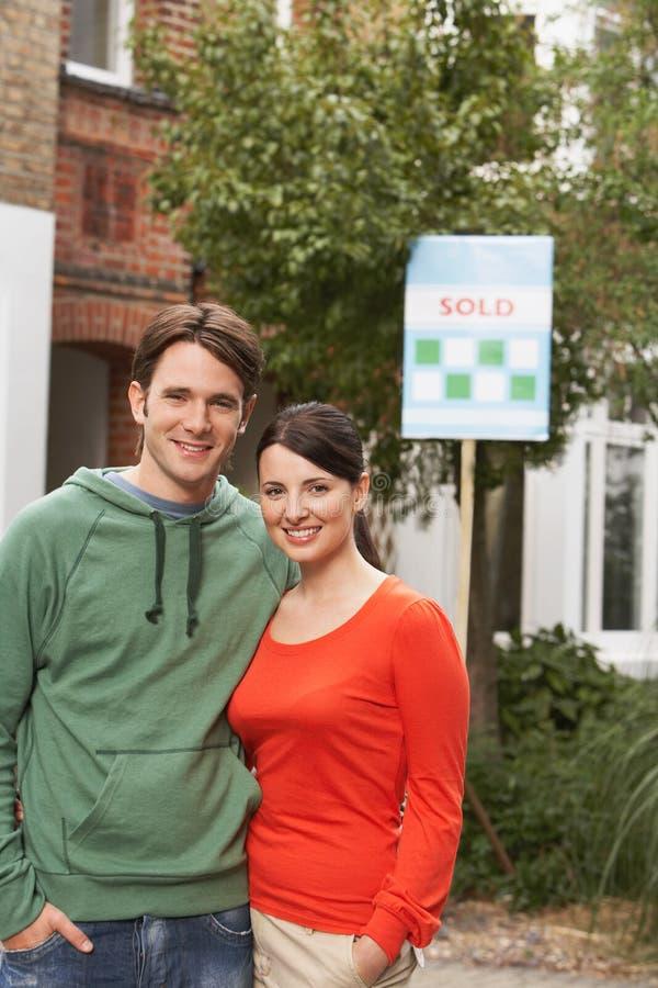Los pares en Front Of New Home With vendieron la muestra imágenes de archivo libres de regalías