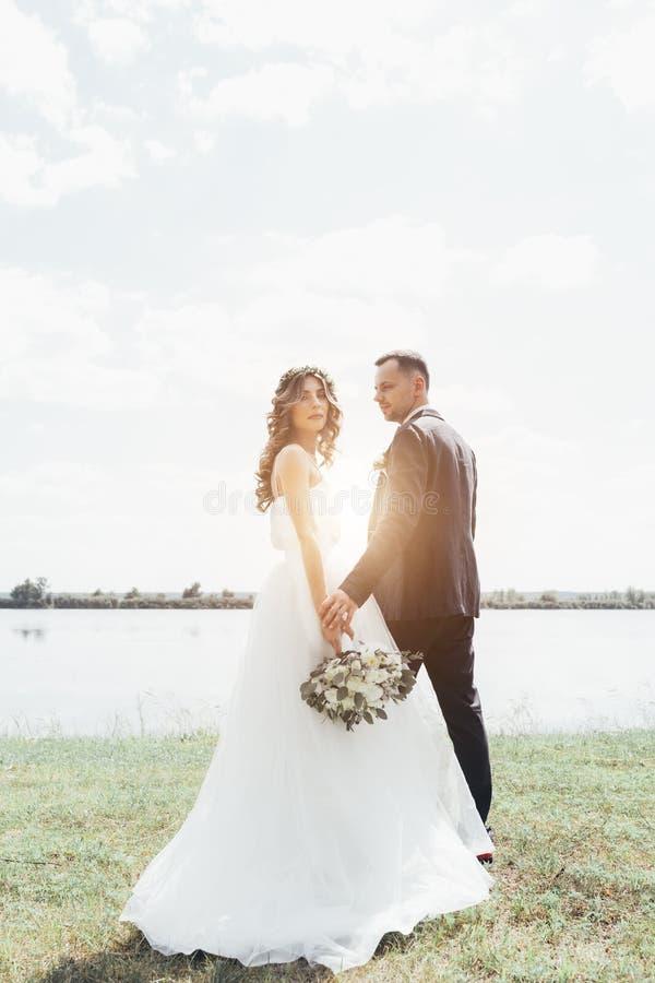 los pares en la boda attire con un ramo de flores fotos de archivo