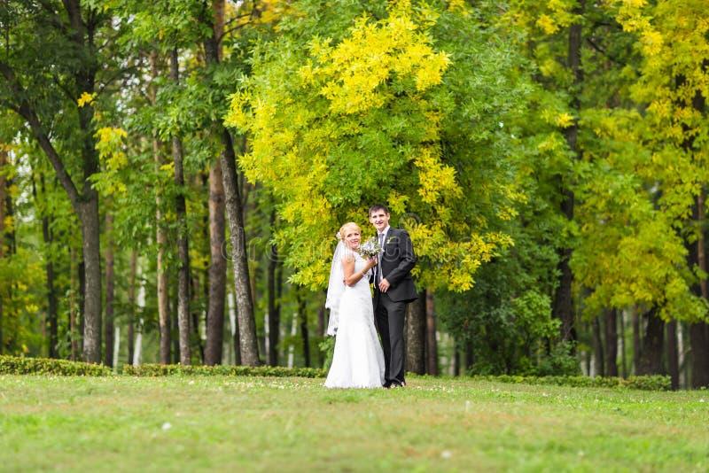 Los pares en la boda attire con un ramo de flores, de novia y de novio al aire libre imagen de archivo libre de regalías