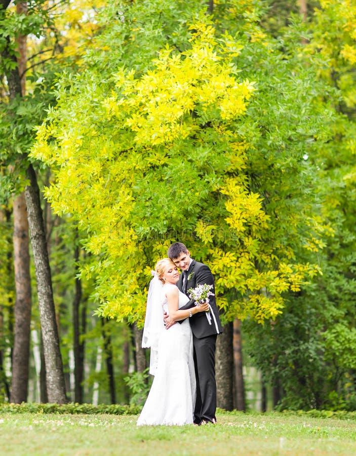 Los pares en la boda attire con un ramo de flores, de novia y de novio al aire libre fotografía de archivo